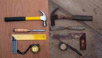 Top view of an old hammer, chisel, tape measure against a set of new handtools on a wooden workbench photo