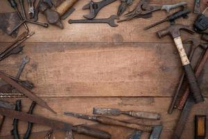 Collection of antique woodworking handtools on a rough old workbench photo