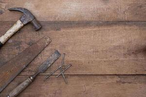 Top view of an old hammer, chisel, and file on an olden wooden workbench photo