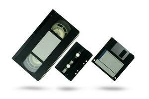 Videocasete, cinta de audio y un disquete sobre un fondo blanco. foto