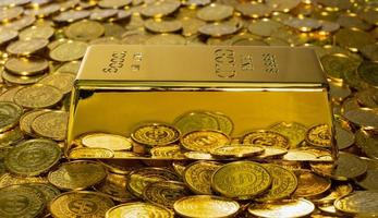 Close up of a shiny 1 kg gold bar on a stack of gold coins photo