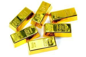 Cerca de brillantes barras de oro de 1 kg sobre un fondo blanco. foto