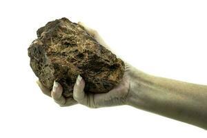Cerca de una mano sosteniendo una piedra aislado sobre un fondo blanco. foto