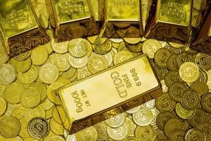Close up of shiny gold bars on stacks of gold coins photo