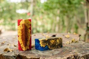 Two casted epoxy resin burl wood cubes on an old table photo