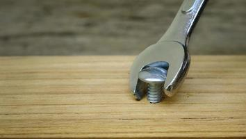Close-up of a wrench screwing a nut into a wooden plank, failing to use the right tool concept