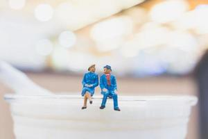 Miniature couple sitting on a cup, Valentine Day's concept