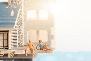 Miniature people staying at home doing self-quarantine to avoid coronavirus, stay home concept photo