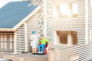 Personas en miniatura que se quedan en casa haciendo auto cuarentena, concepto de estancia en casa foto