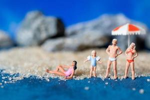 Gente en miniatura vistiendo trajes de baño relajándose en la playa con un fondo azul, concepto de verano foto