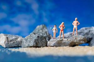 Miniature people wearing swimsuits relaxing on the beach with a blue background, summertime concept photo