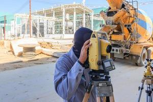 Surveyor worker making measuring with theodolite equipment at construction site. photo