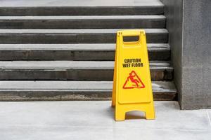Lobby floor with mop bucket and caution wet floor sign