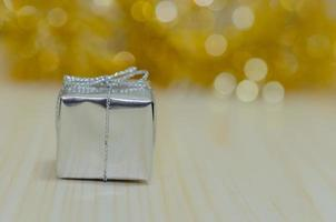 Silver gift against a gold background photo