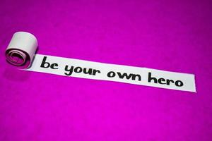 Be your own hero text, Inspiration, motivation and business concept on purple torn paper photo
