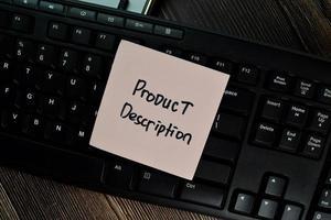 Descripción del producto escrito en una nota adhesiva aislada en el teclado y la mesa de madera foto