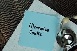 Colitis ulcerosa escrito en una nota adhesiva aislado en la mesa de madera
