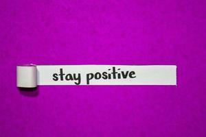 Manténgase positivo con el texto, la inspiración, la motivación y el concepto empresarial en papel rasgado púrpura foto