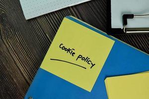 Política de cookies escrita en un papeleo aislado sobre una mesa de madera foto