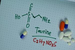 Fórmula química estructural escrita en un libro con píldoras que representan productos químicos foto