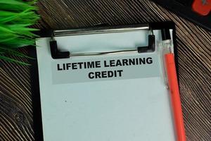 Crédito de aprendizaje de por vida escrito en el papeleo aislado en la mesa de madera