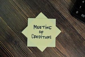 Reunión de acreedores escrito en nota adhesiva aislado sobre mesa de madera