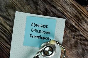 Experiencias adversas de la infancia escritas en una nota adhesiva aislado en la mesa de madera