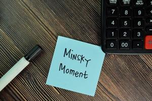 Momento minsky escrito en una nota adhesiva aislado en la mesa de madera