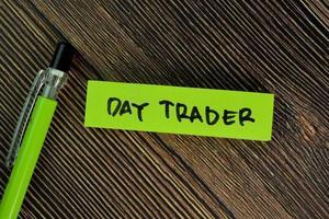 comerciante del día escrito en nota adhesiva aislado en la mesa de madera foto