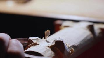 Holzschnitzer schnitzen die Beine mit einem Meißel auf einem Holzständer