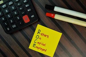 Roce - Retorno del capital empleado escrito en una nota adhesiva aislado en la mesa de madera