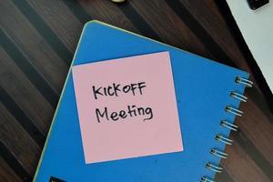 Reunión de inicio escrita en una nota adhesiva aislado en la mesa de madera