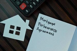 Acuerdo de indulgencia hipotecaria escrito en una nota adhesiva aislado en la mesa de madera
