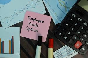 Opción sobre acciones de empleado escrito en nota adhesiva aislado sobre mesa de madera