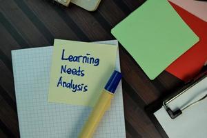 Análisis de las necesidades de aprendizaje escrito en una nota adhesiva aislado en la mesa de madera