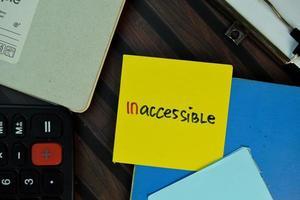 inaccesible escrito en una nota adhesiva aislada en la mesa de madera.