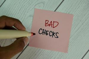 Bad Checks written on sticky note isolated on wooden table photo