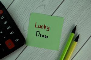 Lucky Draw written on sticky note isolated on wooden table photo