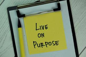 Vivir a propósito escrito en una nota adhesiva aislado en la mesa de madera foto