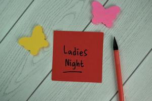 Ladies Night written on sticky note isolated on wooden table