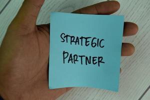 Socio estratégico escrito en una nota adhesiva aislado en la mesa de madera