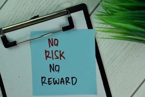 Sin riesgo, sin recompensa, escrito en una nota adhesiva aislado en la mesa de madera foto