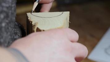 o carpinteiro marca um pedaço de madeira com um lápis.