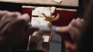 marceneiro retire o excesso de um pedaço de madeira com uma faca