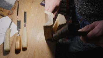 woodworker breaks a piece of wood from a piece of wood with a knife and hammer