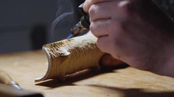 El hombre quema un producto de madera con un quemador. video