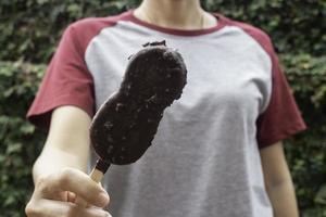 persona sosteniendo un palito de helado de chocolate