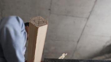 marceneiro aplaina a perna de uma cadeira de madeira