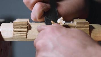 homem retira o excesso de um pedaço de madeira com uma faca video