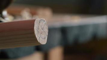 Handwerker plant ein hölzernes Stuhlbein mit einem Handhobel.